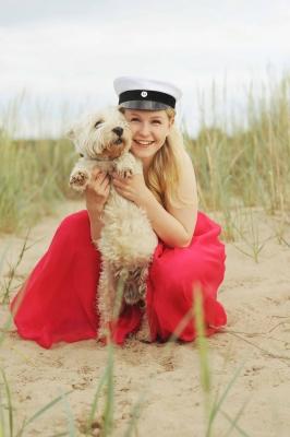 Ylioppilas koiran kanssa rannalla
