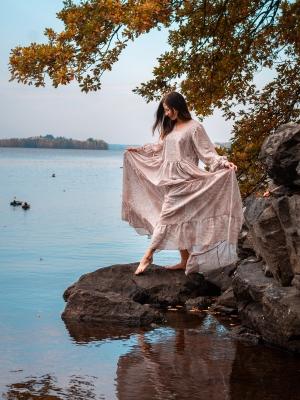 Nainen järven rannalla mekossa