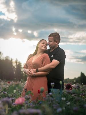 Pariskunta niityllä ilta-auringossa