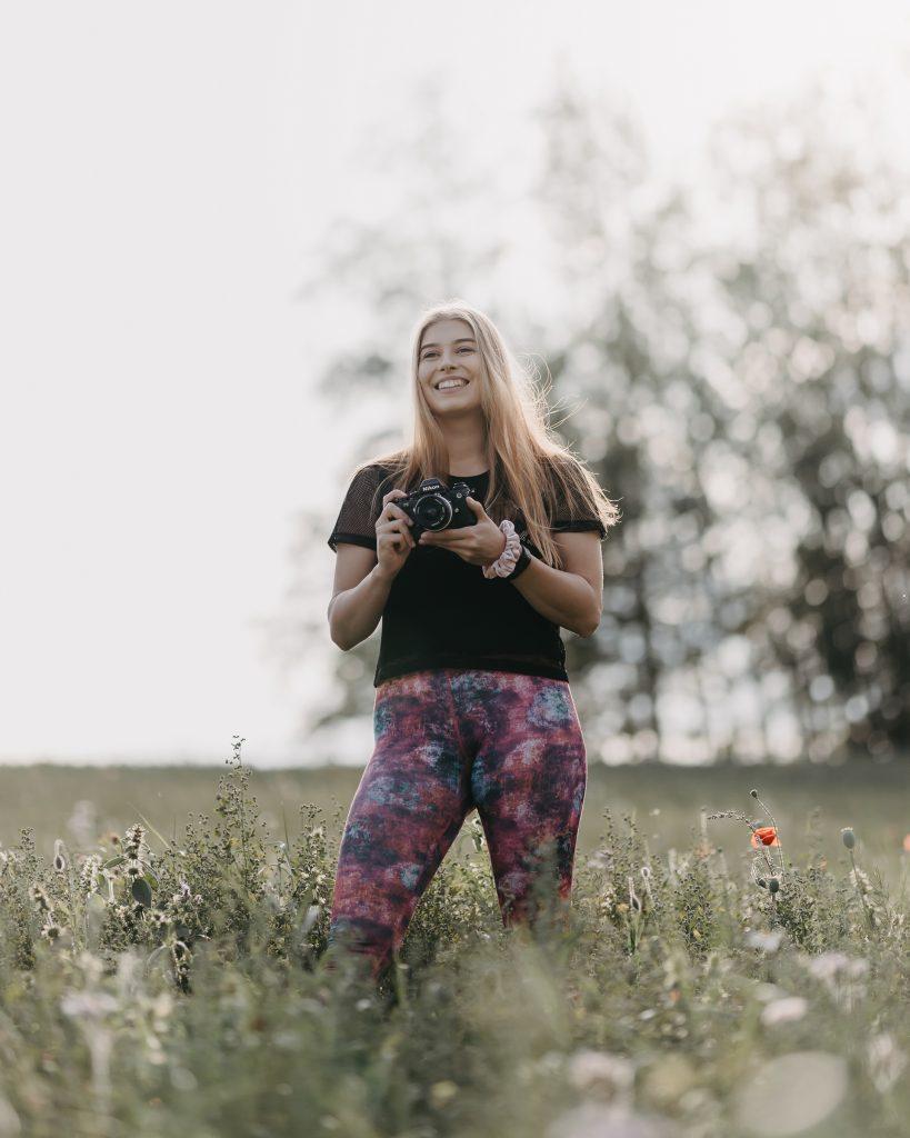 Valokuvaaja Anna niityllä kamera kädessä